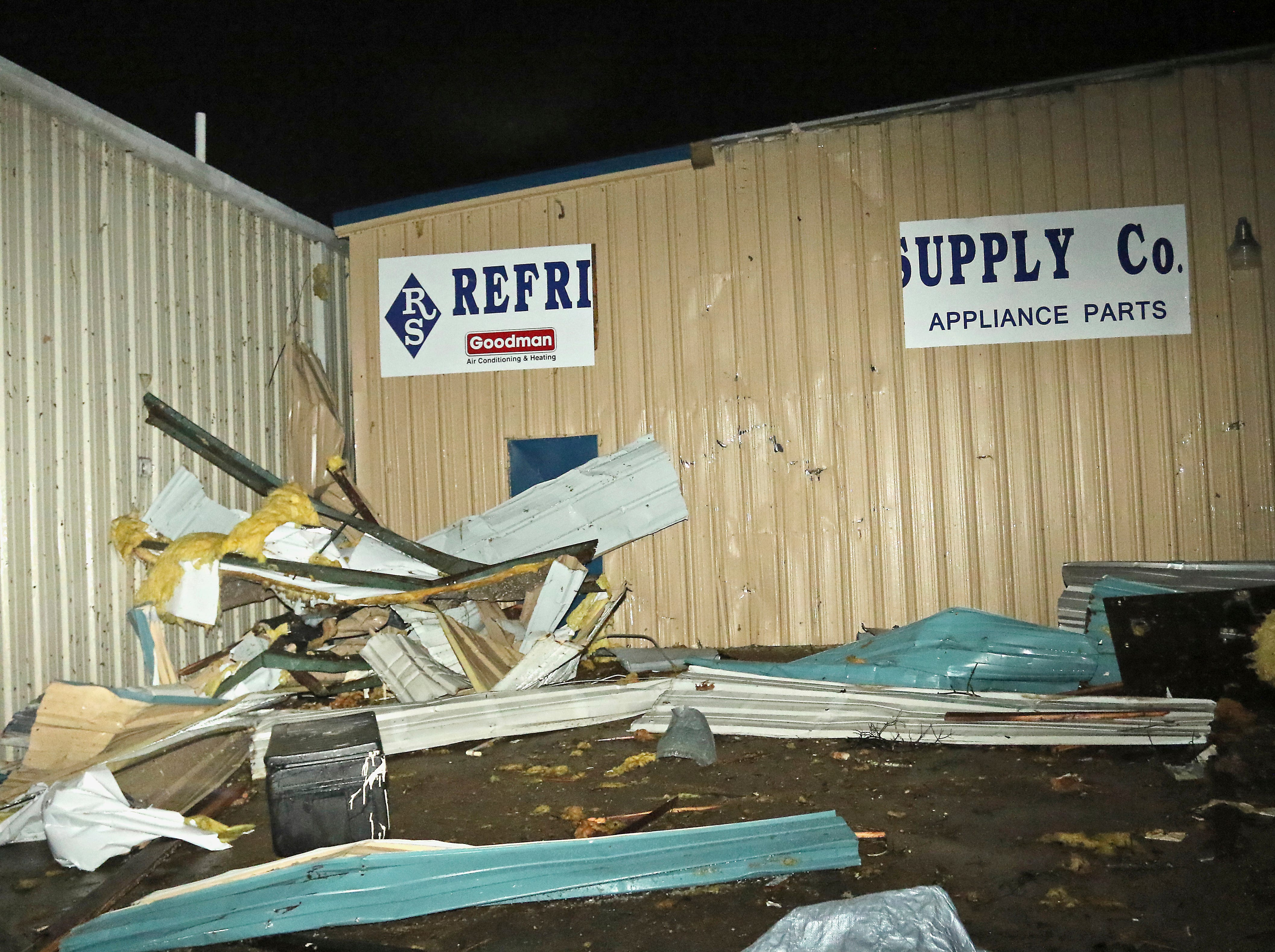 Tin from nearby businesses is piled up in front of Refrigeration Supply on Conway Drive in Columbus, Miss. after a tornado struck the area Saturday, Feb. 23, 2019. (AP Photo/Jim Lytle)
