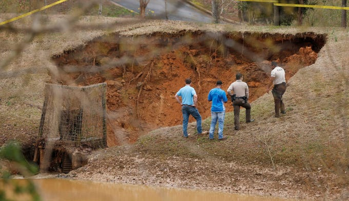 Lafayette County authorities oversee a break in the Audubon Dam in the North Point subdivision in Oxford, Miss., Saturday, Feb. 23, 2019. Homes, highways, parks and bridges throughout the South have been flooded or put out of commission Saturday, as the toll of days of drenching rains swelled waterways and pooled over saturated lands amid a threat of severe storms. (AP Photo/Rogelio V. Solis)