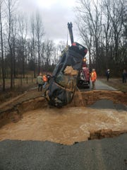 A sinkhole opened on Otha Holt Road between Milan and Medina on Saturday, swallowing one vehicle after its three passengers escaped unharmed.
