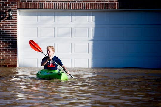 James Webster, of Knoxville, passes by a flooded home next to the Sunoco on Ebenezer Road and Gleason Drive in Knoxville, Tennessee on Sunday, February 24, 2019.