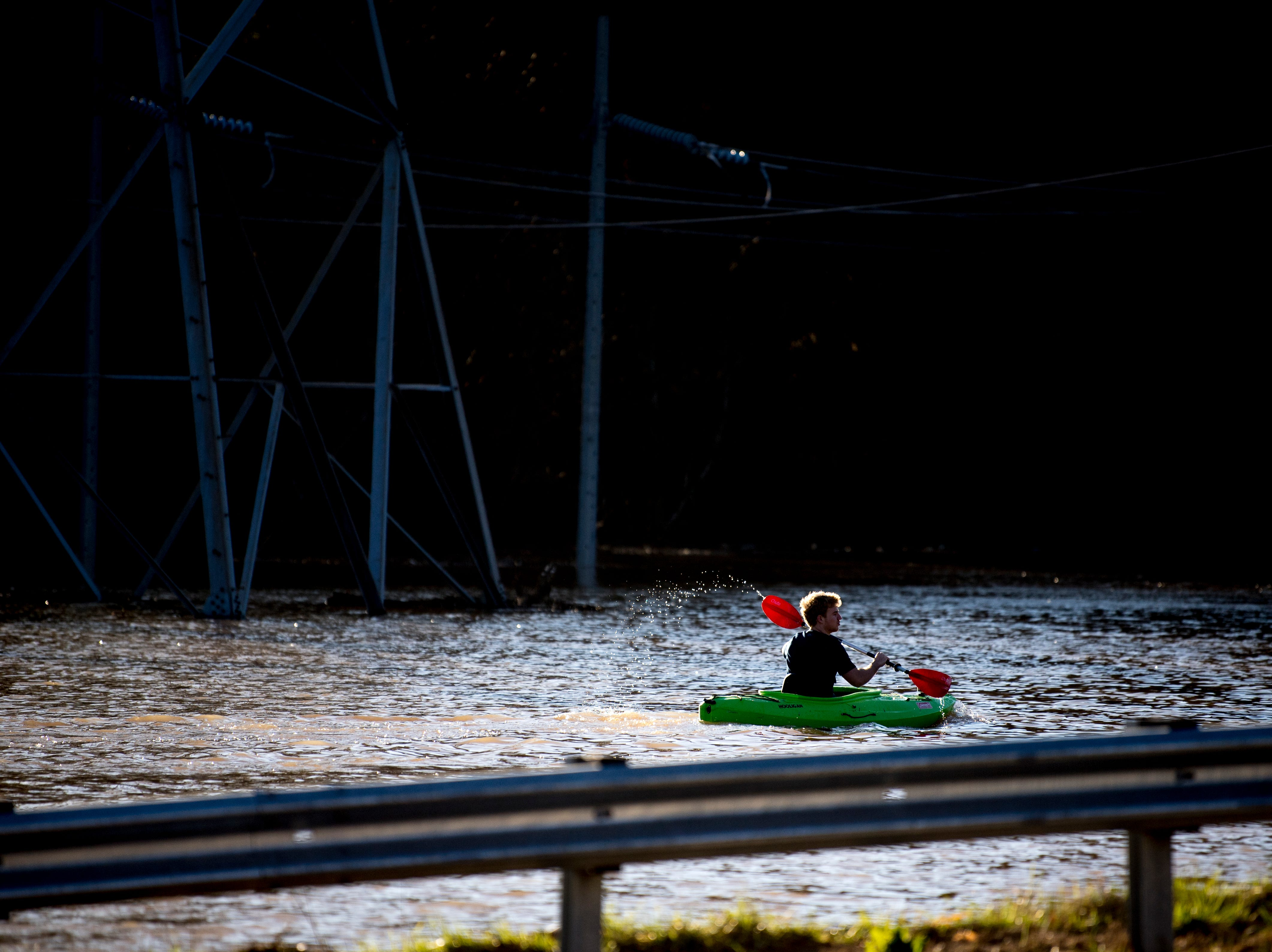 James Webster, of Knoxville, kayaks beneath power lines near the Sunoco on Ebenezer Road and Gleason Drive in Knoxville, Tennessee on Sunday, February 24, 2019.