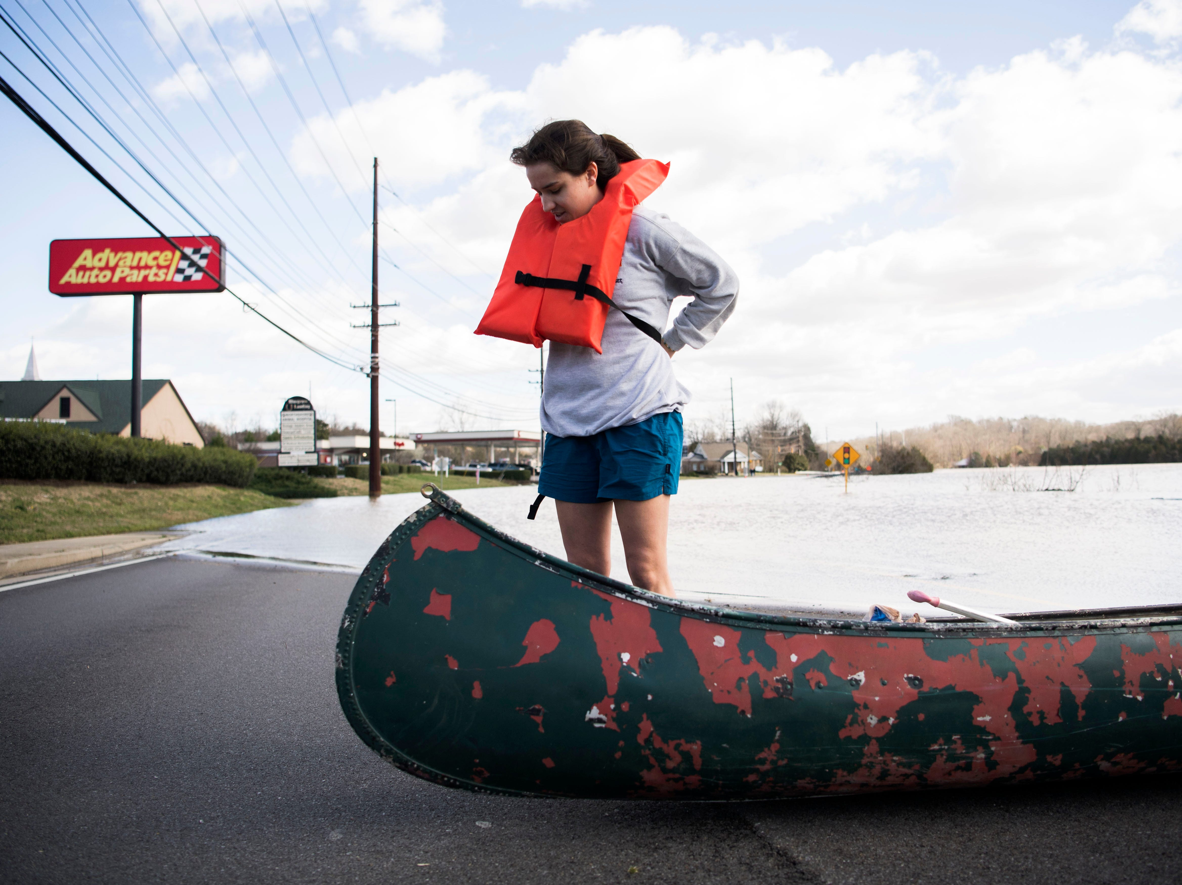 Julia Bryant, 18, of Knoxville, puts on her life vest before canoeing to her home which was surrounded by flood waters off Lantair Farm Lane, in Southwest Knox County Sunday, Feb. 24, 2019.