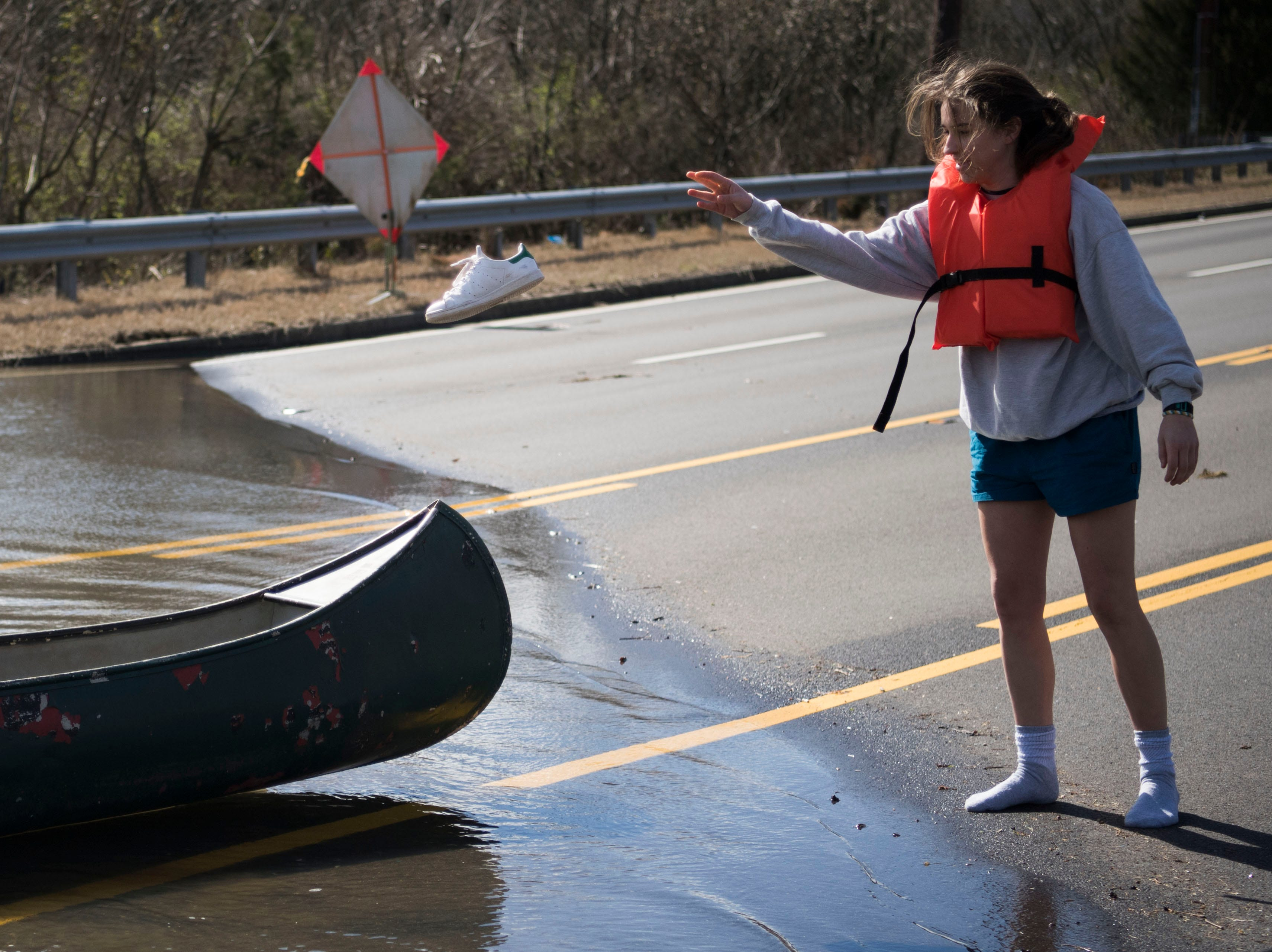 Julia Bryant, 18, of Knoxville, throws her shoes into the boat before canoeing to her home which was surrounded by flood waters off Lantair Farm Lane, in Southwest Knox County Sunday, Feb. 24, 2019.
