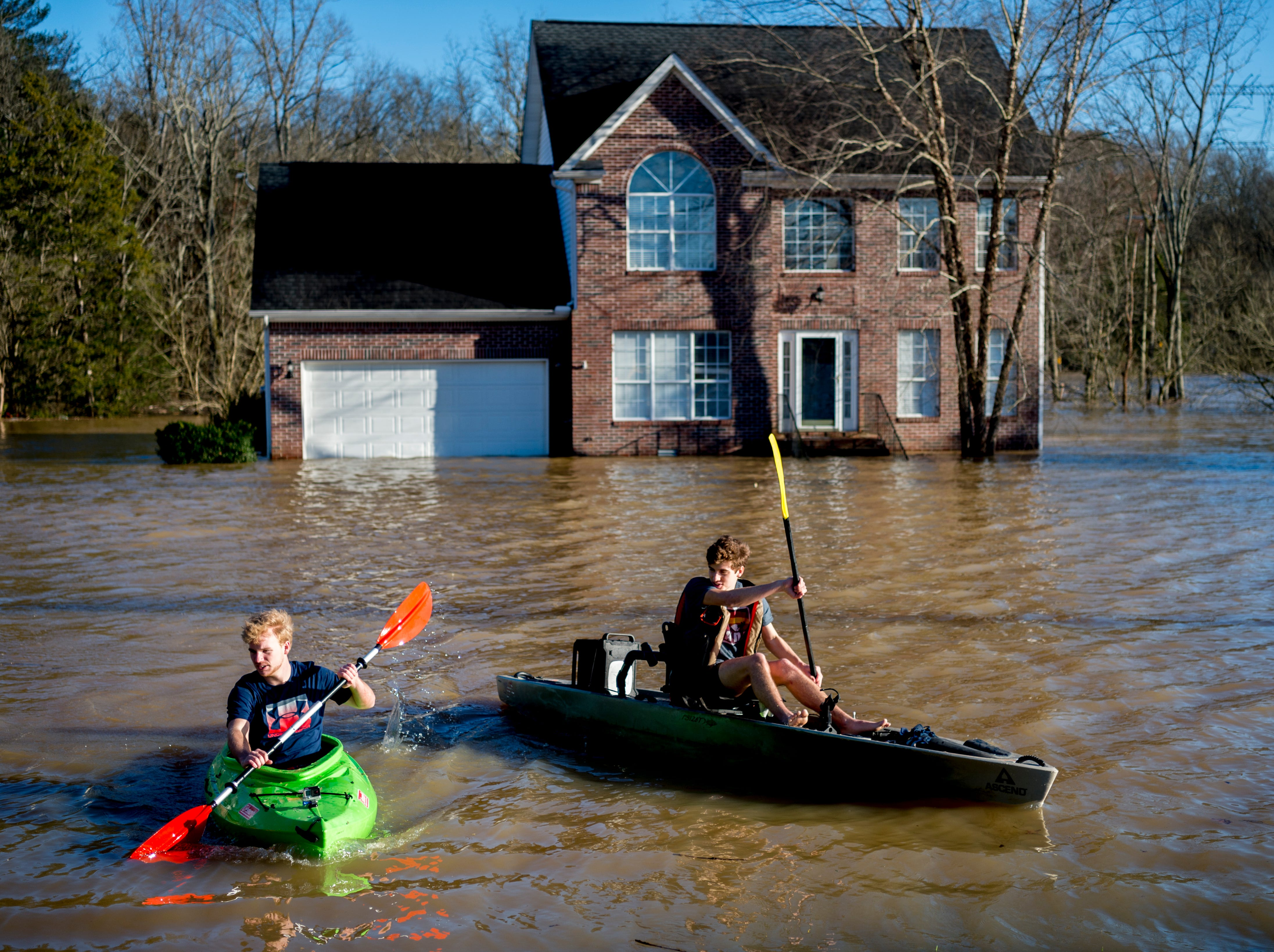 Truman Douglass and James Webster, both from Knoxville, pass by a flooded home next to the Sunoco on Ebenezer Road and Gleason Drive in Knoxville, Tennessee on Sunday, February 24, 2019.