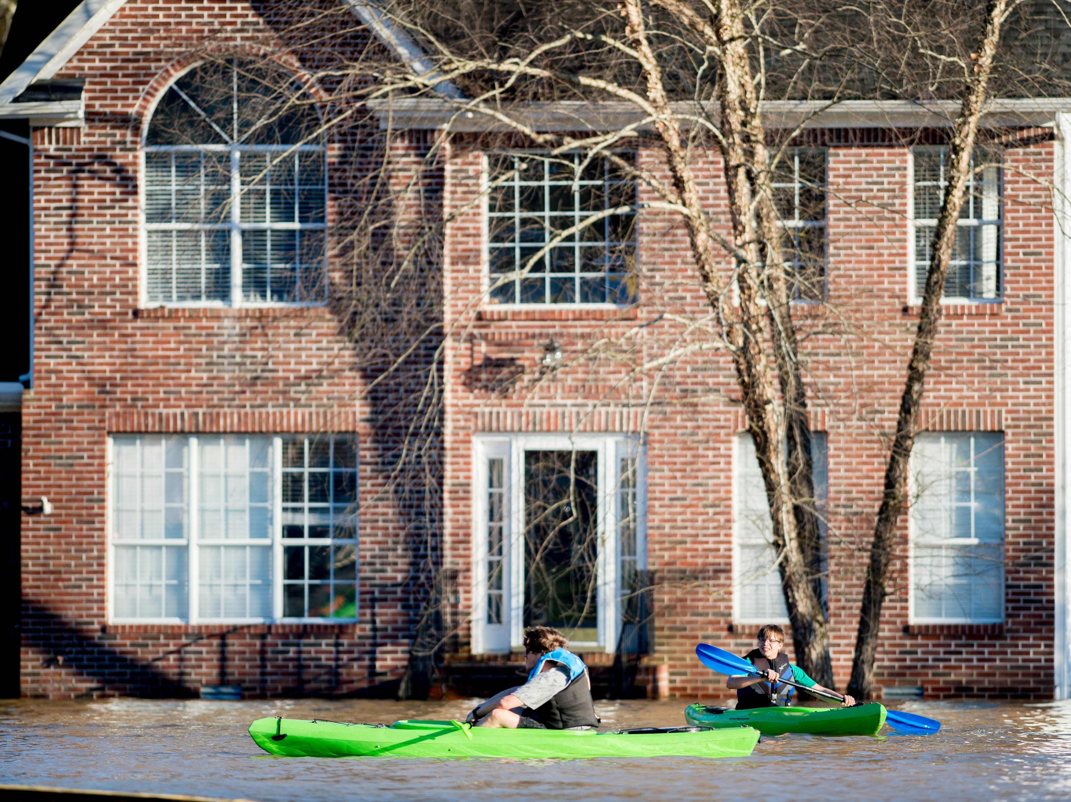 Anthony Forrey and his cousin Jordan Landsman, both from Knoxville, paddle in front of a flooded home near the Sunoco on Ebenezer Road and Gleason Drive in Knoxville, Tennessee on Sunday, February 24, 2019.