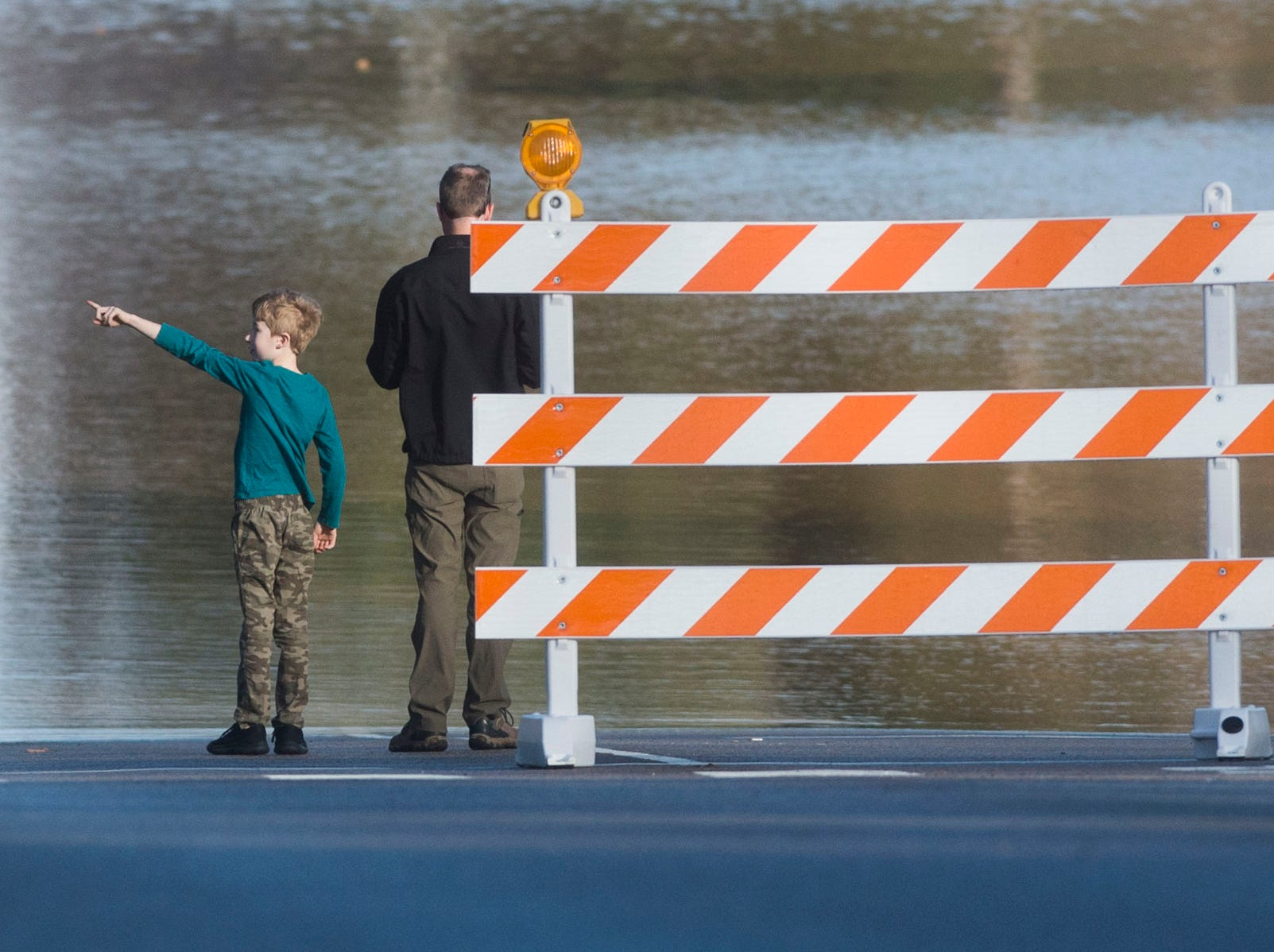 Harrison McReynolds, 8, of Knoxville, and his father Matthew, observe the continued flooding on South Peters and Ebenezer Road in West Knoxville Sunday, Feb. 24, 2019.