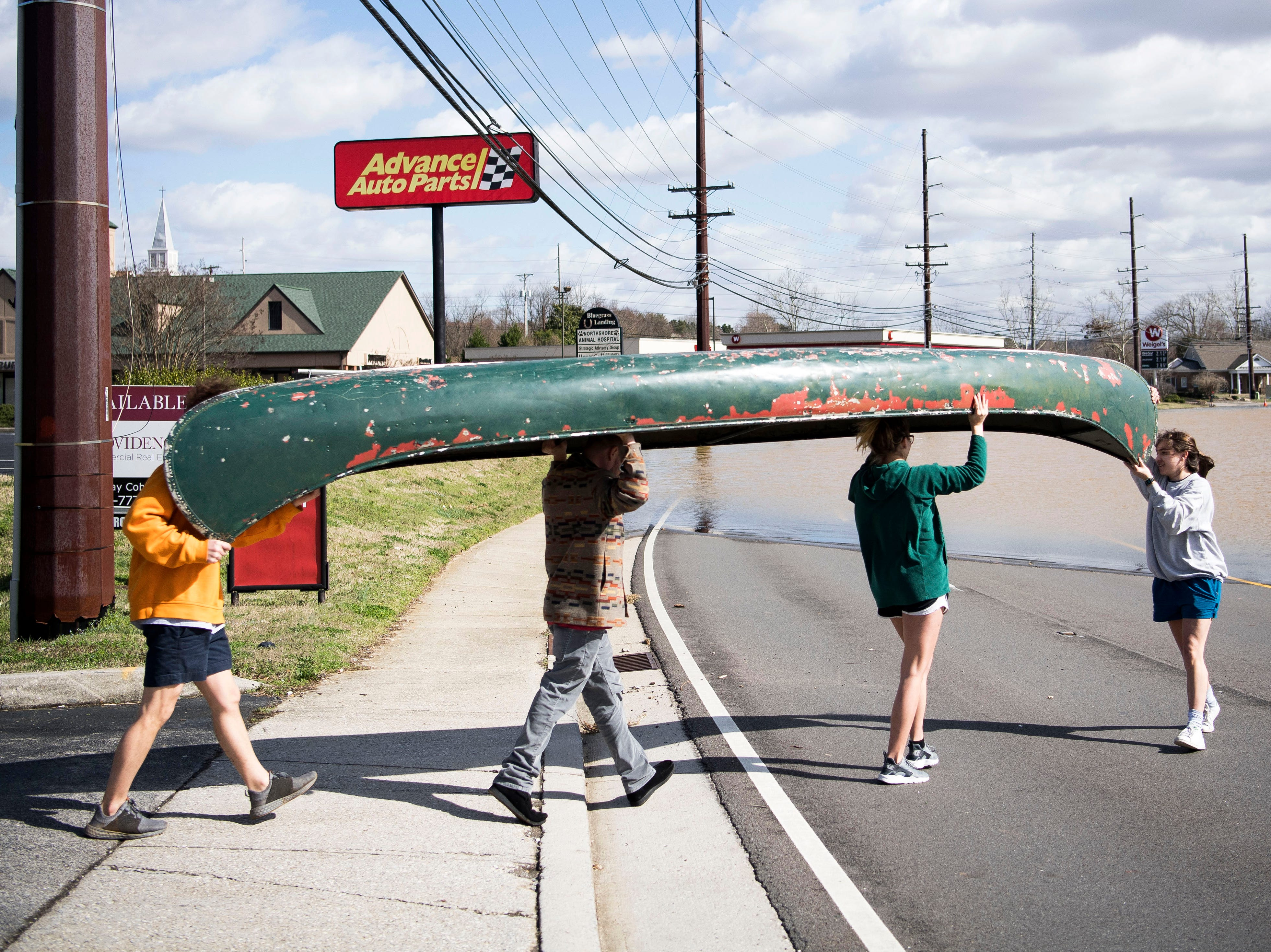 At right Julia Bryant, 18, of Knoxville, leads friends in helping her put a canoe into flood waters on South Northshore Drive in Southwest Knox County Sunday, Feb. 24, 2019.  Bryant canoed to her home off Lantair Farm Lane,  which was surrounded by flood waters.  Bryant canoed approximately three-quarters of a mile.