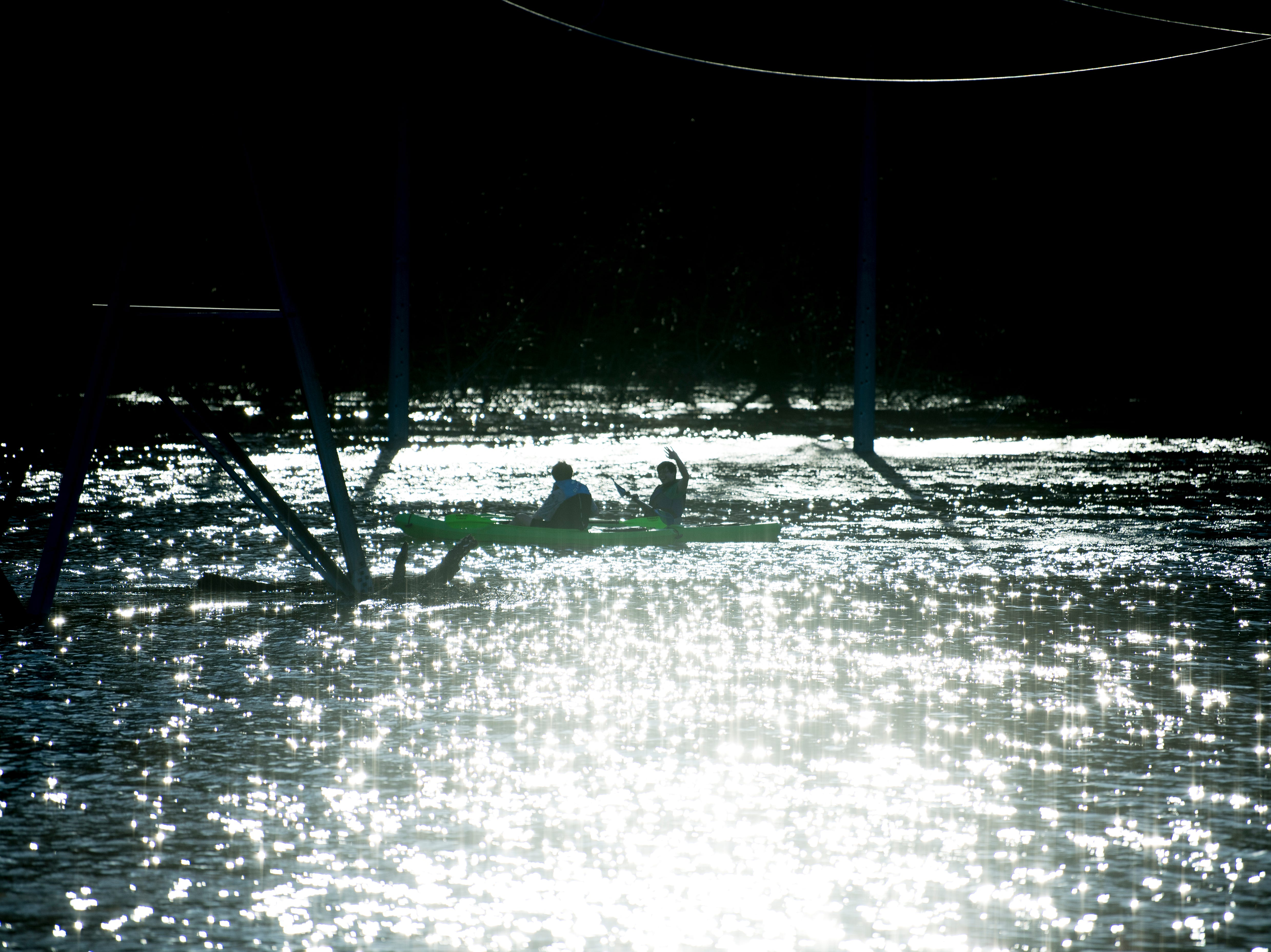 Kayakers wave from the distance while paddling beneath power lines near the Sunoco on Ebenezer Road and Gleason Drive in Knoxville, Tennessee on Sunday, February 24, 2019.