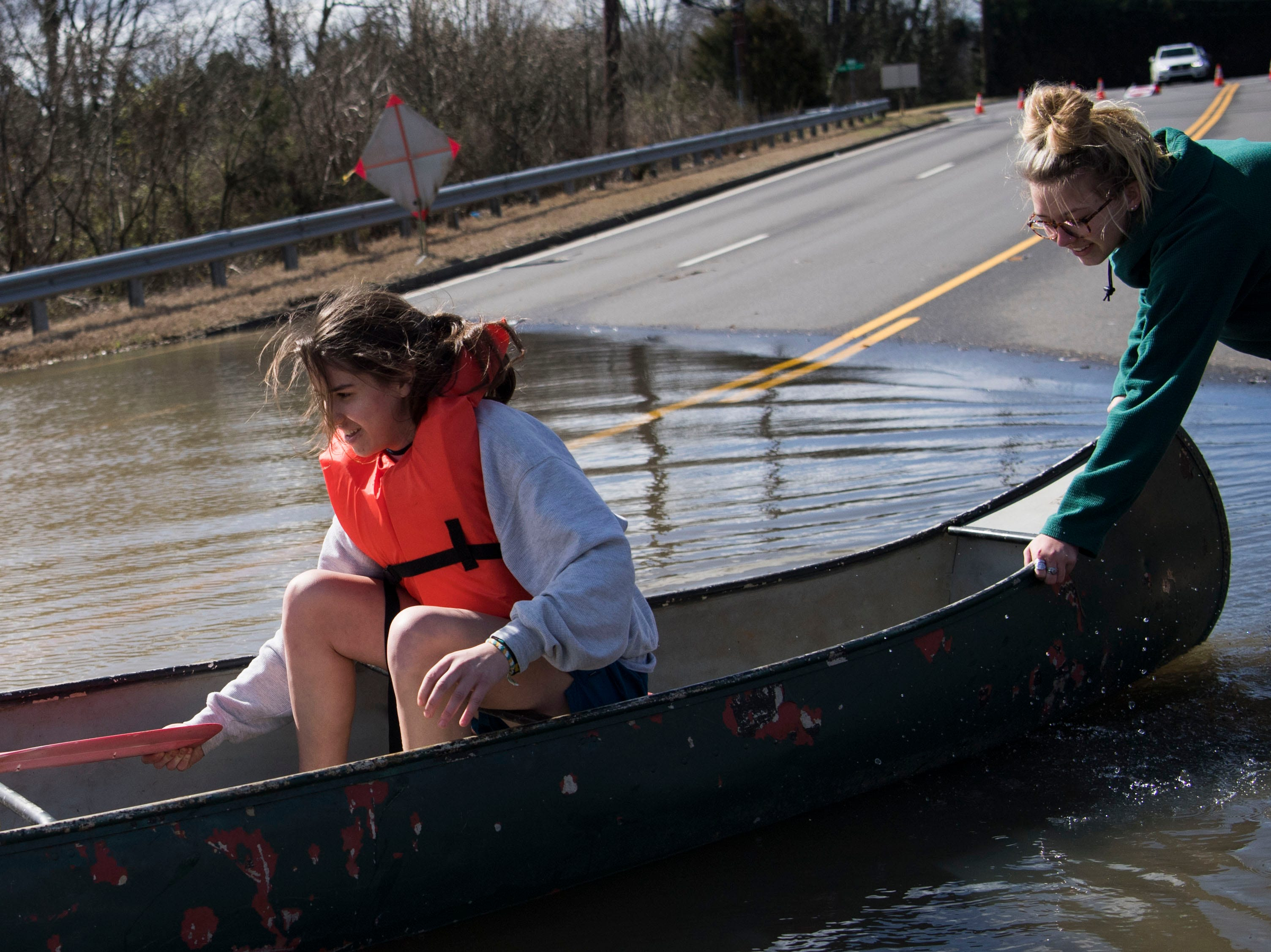 Ansley Pacetti, 18, pushes off her friend Julia Bryant, 18, into flood waters on South Northshore Drive in Southwest Knox County Sunday, Feb. 24, 2019.Bryant canoed to her home which was surrounded by flood waters off Lantair Farm Lane, approximately three-quarters of a mile away.