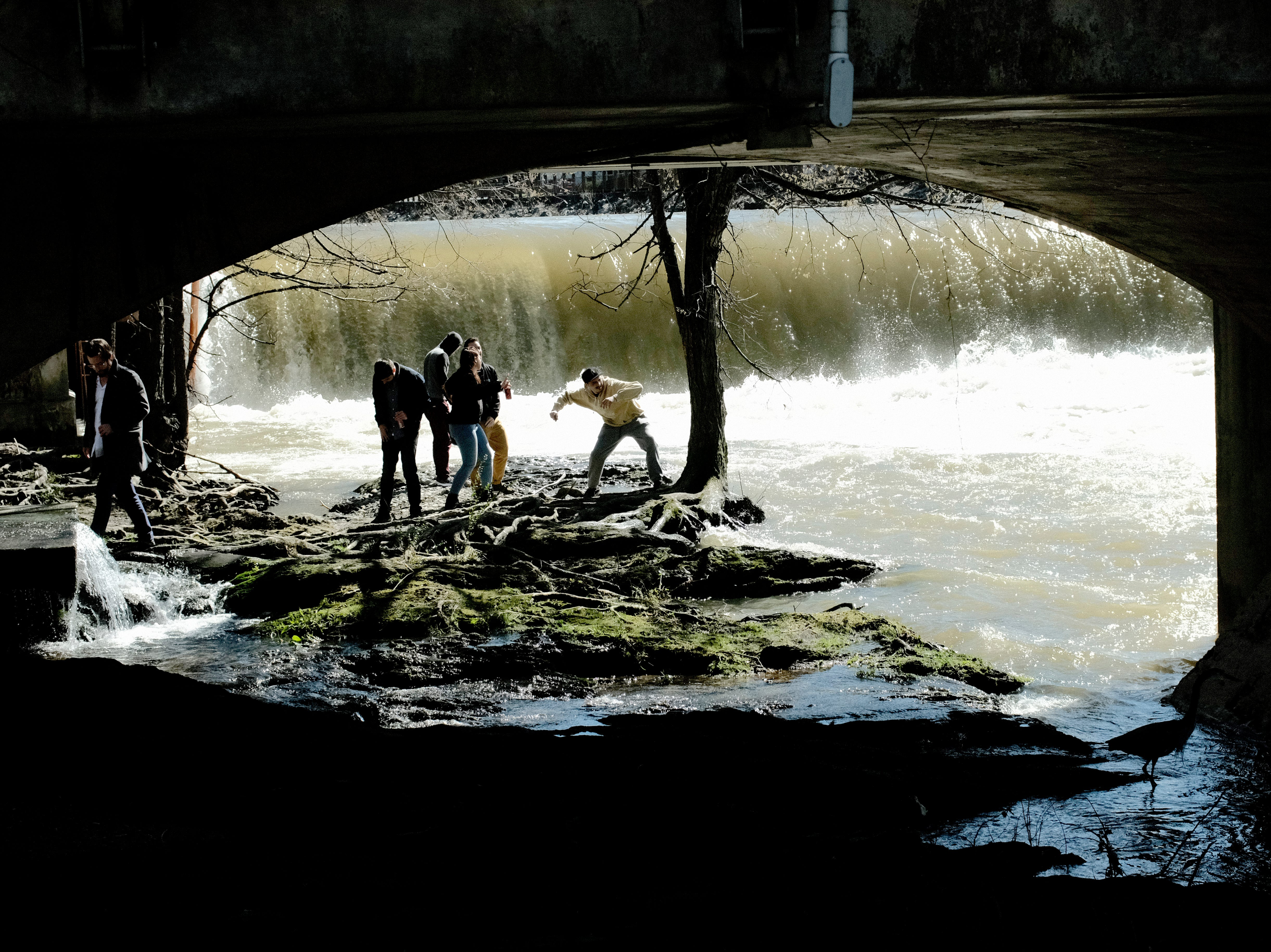 Visitors throw stones into the Little Pigeon River beside the Old Mill Restaurant's overflowing waterfall in Pigeon Forge, Tennessee on Sunday, February 24, 2019.