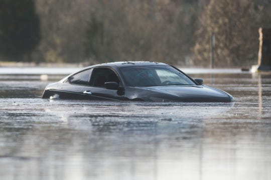 A car is partially submerged in water as flooding continues on South Peters and Ebenezer Road in West Knoxville Sunday, Feb. 24, 2019.