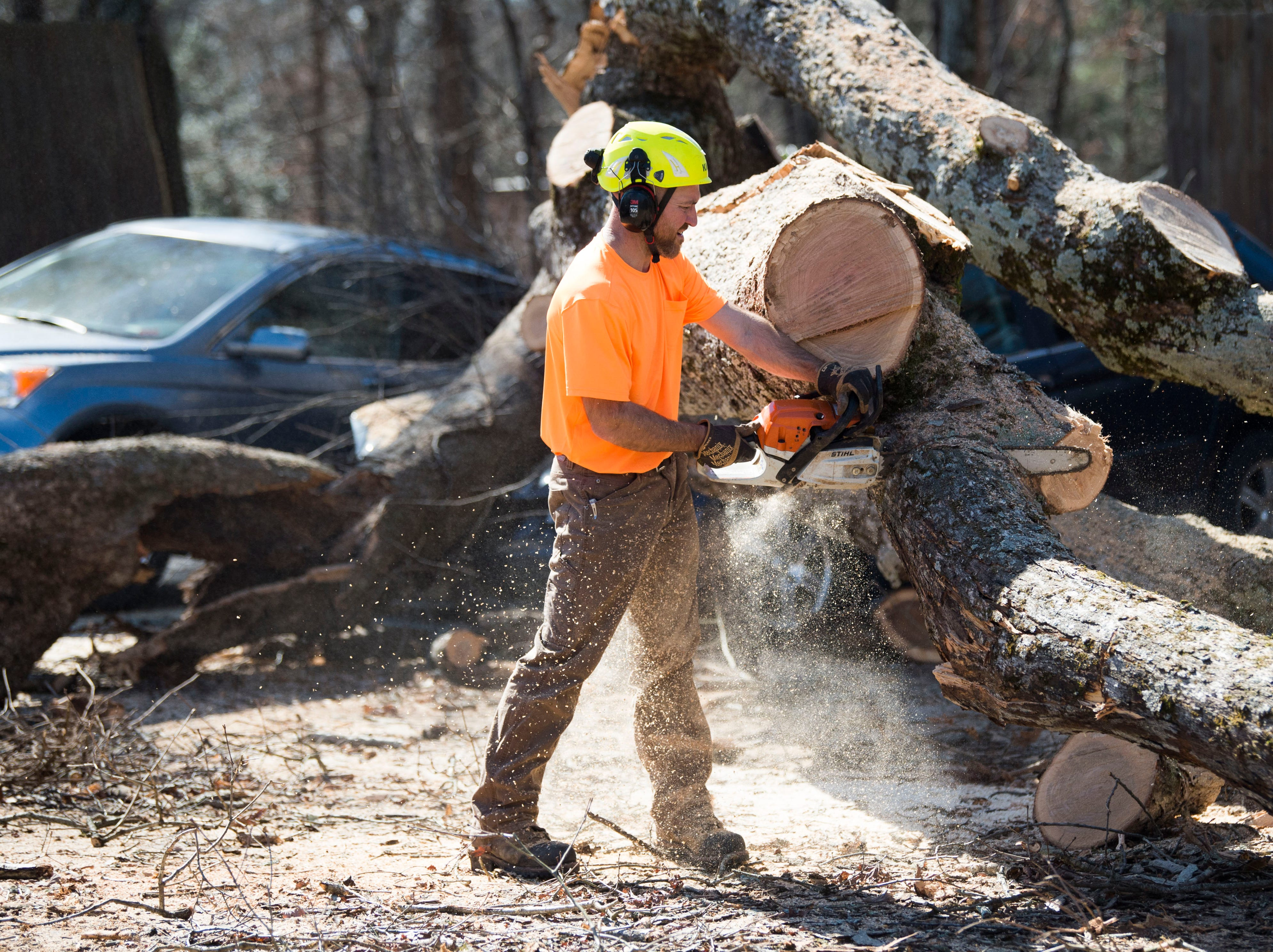 Jason Stiltner of Big Orange Tree takes a chainsaw to a tree which fell on cars during a church service at Fellowship Church Knoxville on Middlebrook Pike Sunday, Feb. 24, 2019. More than twenty cars were affected by the fallen tree.