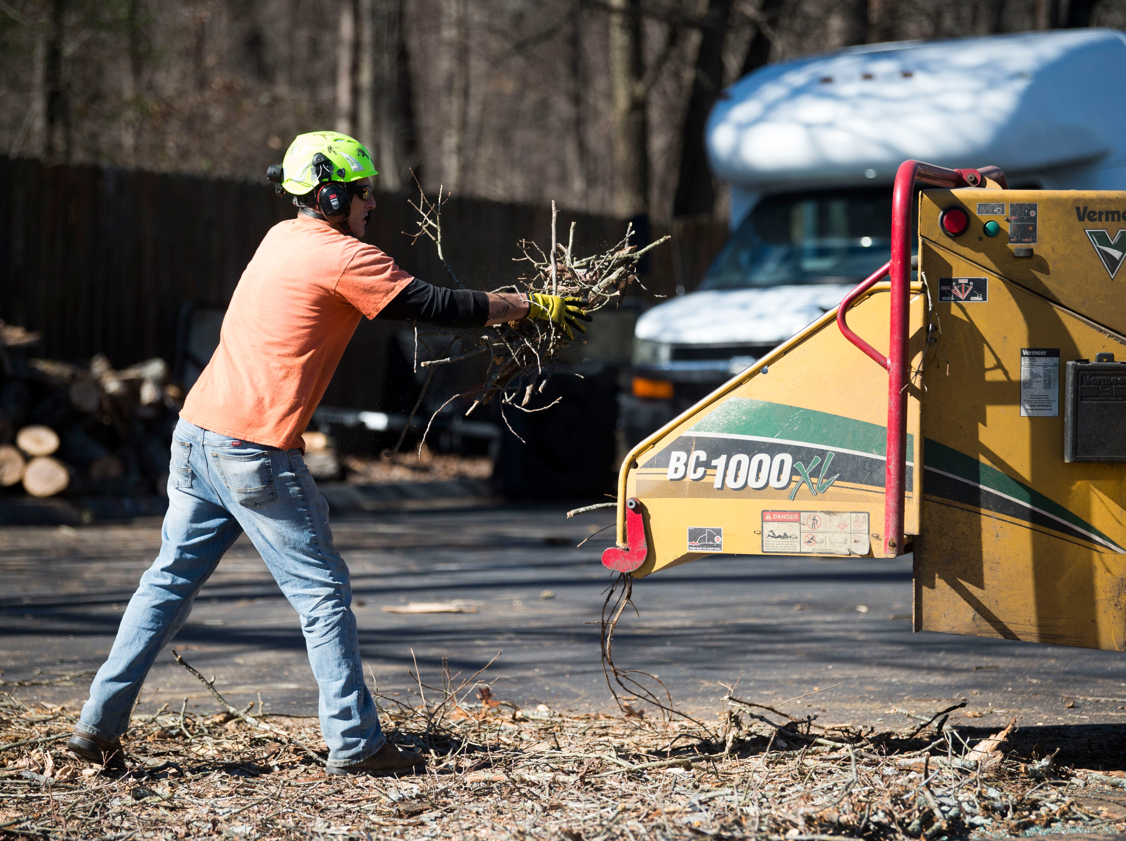 A worker from Big Orange Tree clears debris from a tree which fell during a church service at Fellowship Church Knoxville on Middlebrook Pike Sunday, Feb. 24, 2019. Over twenty cars were affected by the fallen tree.