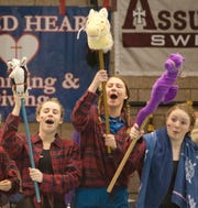 """Sacred Heart swimmers hold up horses on poles as they root for one of their swimmers in the KHSAA state girls swimming and diving championships. The horses were in keeping with their theme, """"It's not our first rodeo.""""  Sacred Heart won the championships again this year, their 7th consecutive state swimming and diving championship.22 February 2019"""