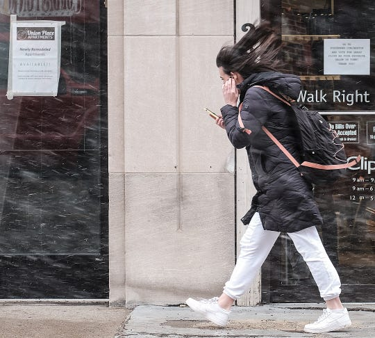 Strong winds blow the snow and this womans hair around in East Lansing Sunday, Feb. 24, 2019. The area is under a High Wind Warning with gusts reaching as high as 65 mph.