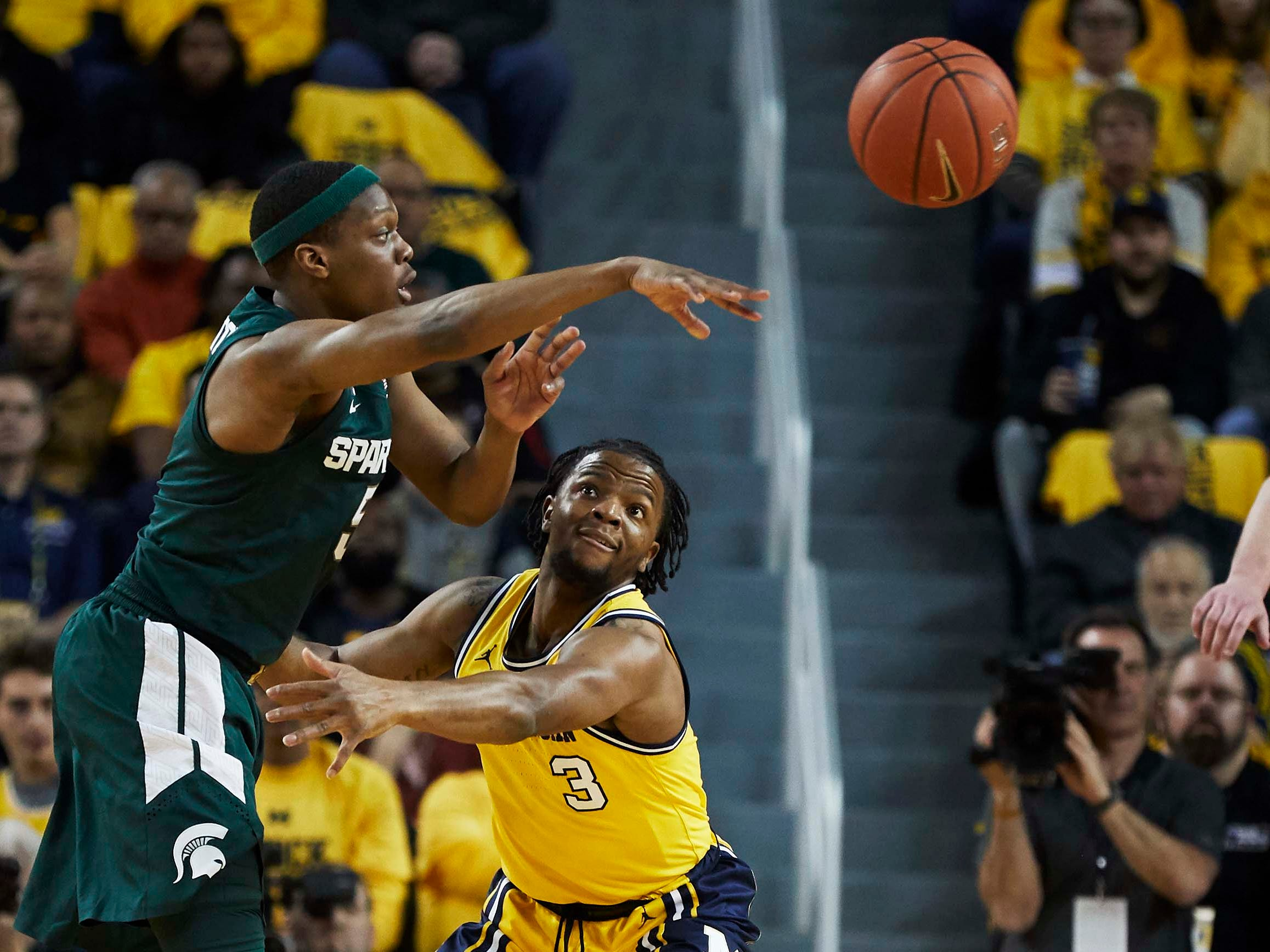 Michigan State Spartans guard Cassius Winston (5) passes on Michigan Wolverines guard Zavier Simpson (3) in the first half at Crisler Center.