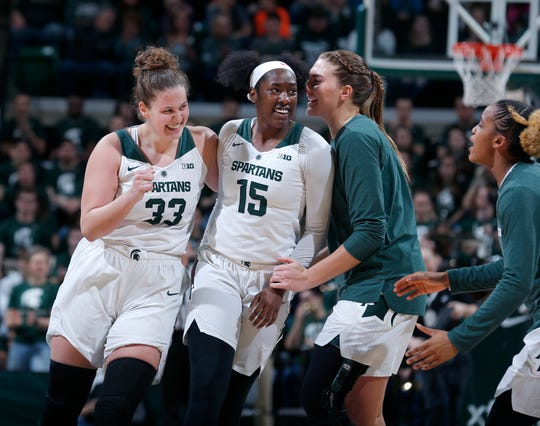 Michigan State's Jenna Allen, from left, Victoria Gaines (15), Kayla Belles and Shay Colley celebrate during the first quarter of an NCAA college basketball game against Michigan, Sunday, Feb. 24, 2019, in East Lansing, Mich. Michigan State won 74-64. (AP Photo/Al Goldis)