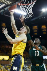 Michigan's Ignas Brazdeikis scores in front of MSU's Gabe Brown on Feb. 24.