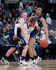 Michigan State's Shay Colley, center, escapes pressure by Michigan's Nicole Munger, left, and Naz Hillmon during the fourth quarter of an NCAA college basketball game, Sunday, Feb. 24, 2019, in East Lansing, Mich.