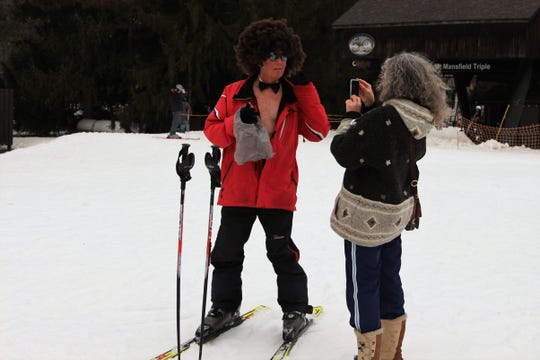 Larry Steele poses for a picture next to Mount Mansfield taken by his partner Maggi Klein. The 72-year-old from Akron braved the cold as he went down a small hill on Saturday wearing only a speedo, a bow tie and a curly brown wig.