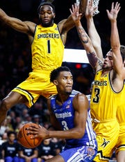 Memphis guard Jeremiah Martin (middle) looks to make a pass against Wichita State defenders Markis McDuffie (left) and Ricky Torres (right).