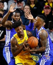 Memphis defenders Raynere Thornton (left) and Kyvon Davenport (right) apply pressure to Wichita State forward Rod Brown (middle) during action Wichita, Kansas, Saturday, February 23, 2019.