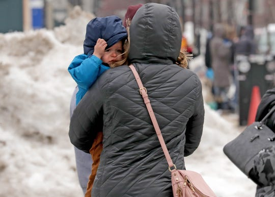 Gavin Southard shields himself from the wind as he is carried by his mother, Jackie Southard, of Delafield as they cross West Kilbourn Avenue on their way to the Shrine Circus at the UW-Milwaukee Panther Arena in Milwaukee on Sunday. Very strong westerly winds developed in the area with gusts up to 60 mph, according to the National Weather Service. Photo by Mike De Sisti/Milwaukee Journal Sentinel