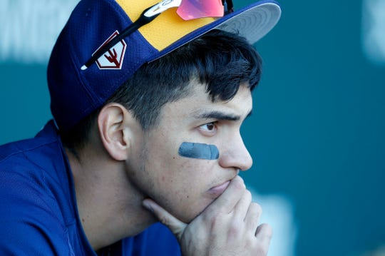 Milwaukee Brewers shortstop Mauricio Dubon watches from the dugout in the third inning during a spring training game against the Chicago Cubs at Sloan Park on Feb. 23, 2019.
