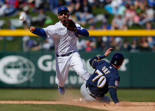 Chicago Cubs second baseman Daniel Descalso turns the double play while avoiding Milwaukee Brewers second baseman Nate Orf in the third inning during a spring training game at Sloan Park on Feb 23, 2019.