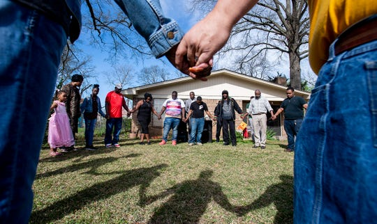 Family and friends hold hands during a prayer at a vigil for Greg Gunn in front of the Gunn family home in Montgomery, Ala. on Sunday February 24, 2019. Gunn was shot and killed by Montgomery police officer Aaron Cody Smith in February 2016.