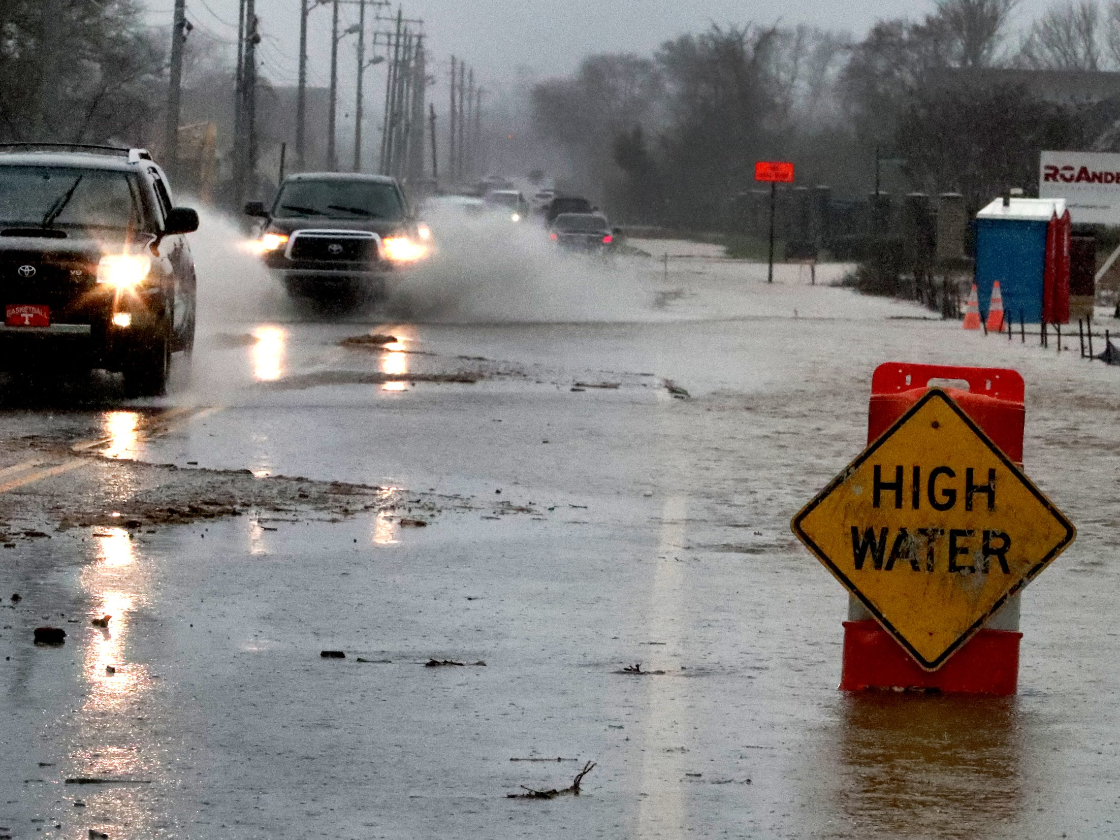 Cars drive down St. Andrews  Drive where water is over the road in Murfreesboro Saturday, Feb. 23, 2019, after days of rain have hit Middle Tennessee. The road was closed later in the day.