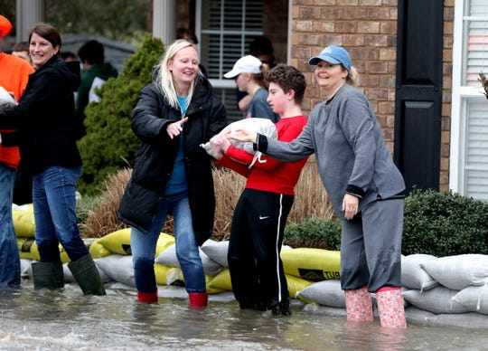 Katja Hedding, left, Allen Green, 13, center and Teresa Garrison, right stack sand bags to keep their neighbor's house safe from flood waters on Steelson Way in Murfreesboro, on Saturday, Feb. 23, 2019.