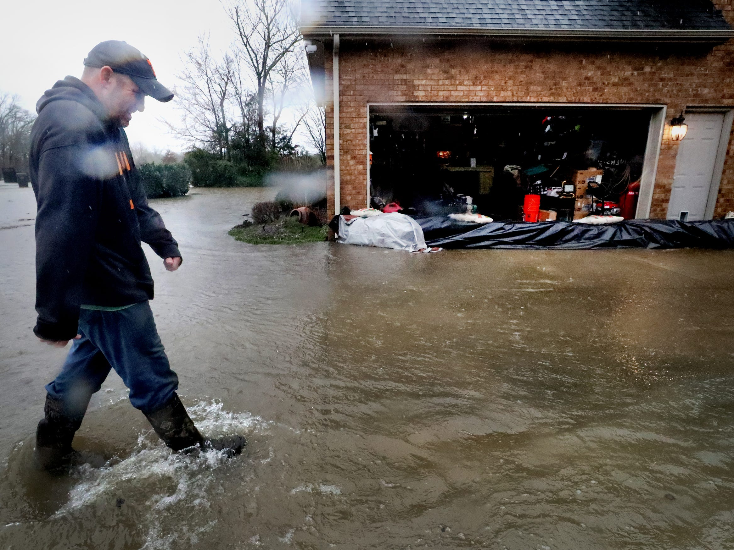 Dan Kellum surveys water surrounding his house along Steelson Way in Murfreesboro Saturday, Feb. 23, 2019, after days of rain have hit Middle Tennessee.