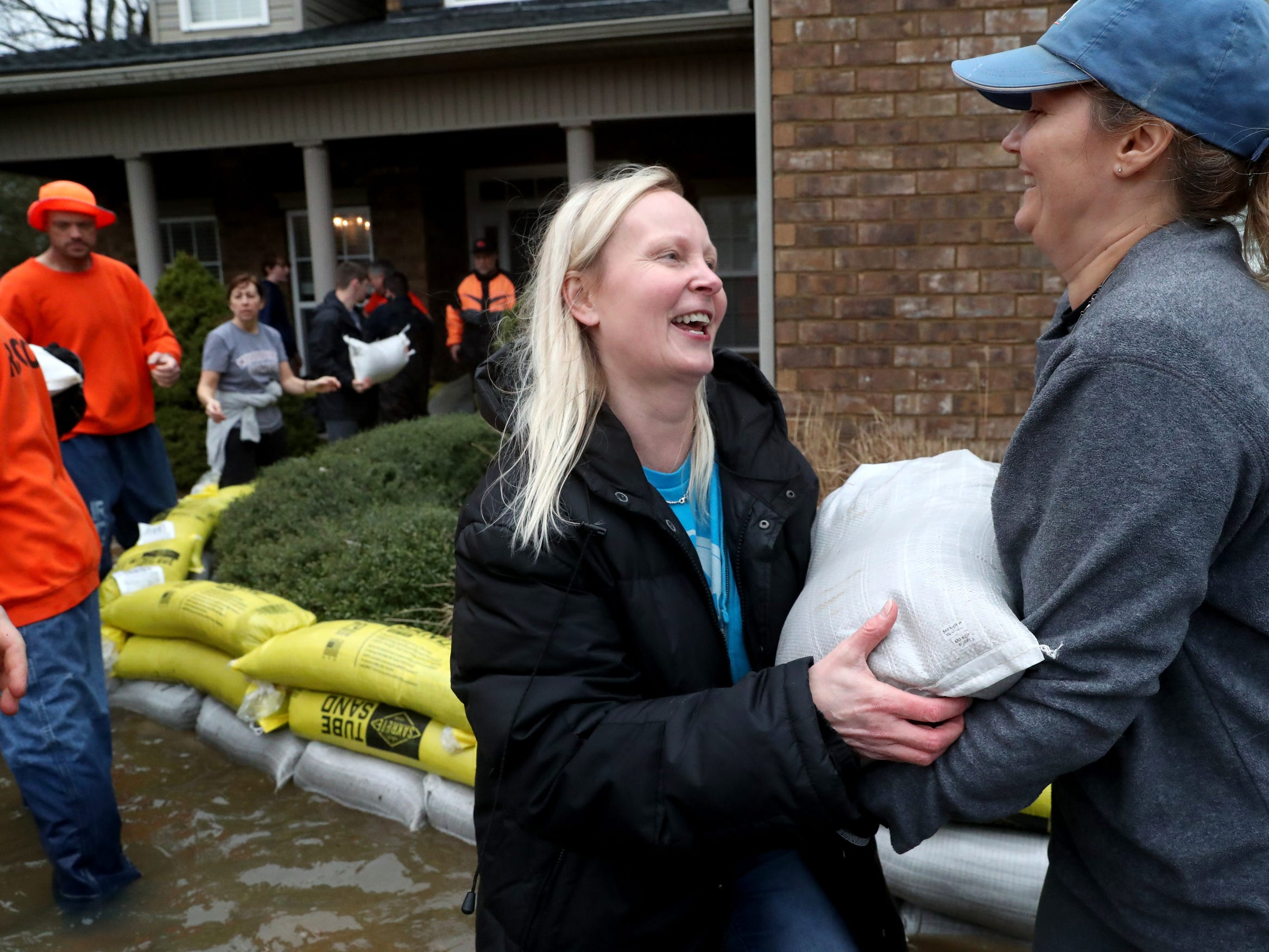 Katja Hedding, left,  and Teresa Garrison, right move sand bags in a line to place around a neighbor's home to keep it safe from flood waters on Steelson Way in Murfreesboro, on Saturday, Feb. 23, 2019.