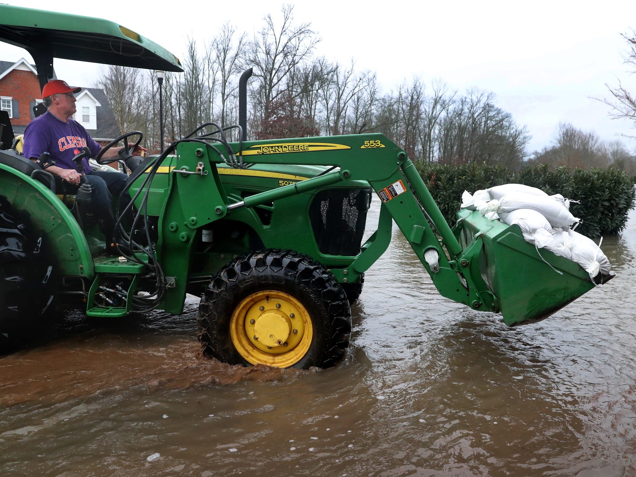 Sand bags are moved by tractor to a home on Steelson Way in Murfreesboro, on Saturday, Feb. 23, 2019, to help protect a home.