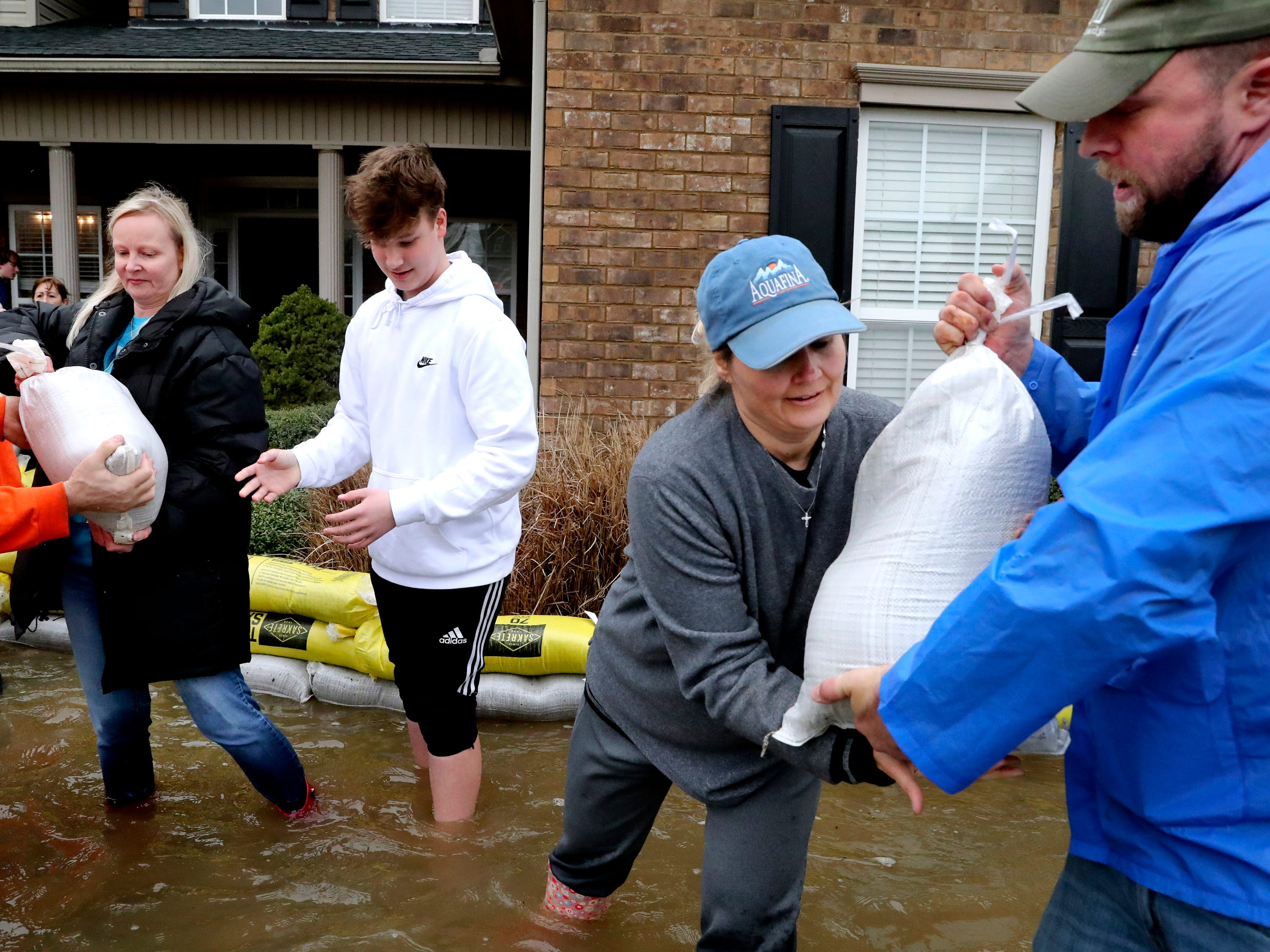 (L to R) Katja Hedding, left, Oliver Hedding, 14, and Teresa Garrison, and Michael Derby stack sand bags to keep their neighbor's house safe from flood waters on Steelson Way in Murfreesboro, on Saturday, Feb. 23, 2019.