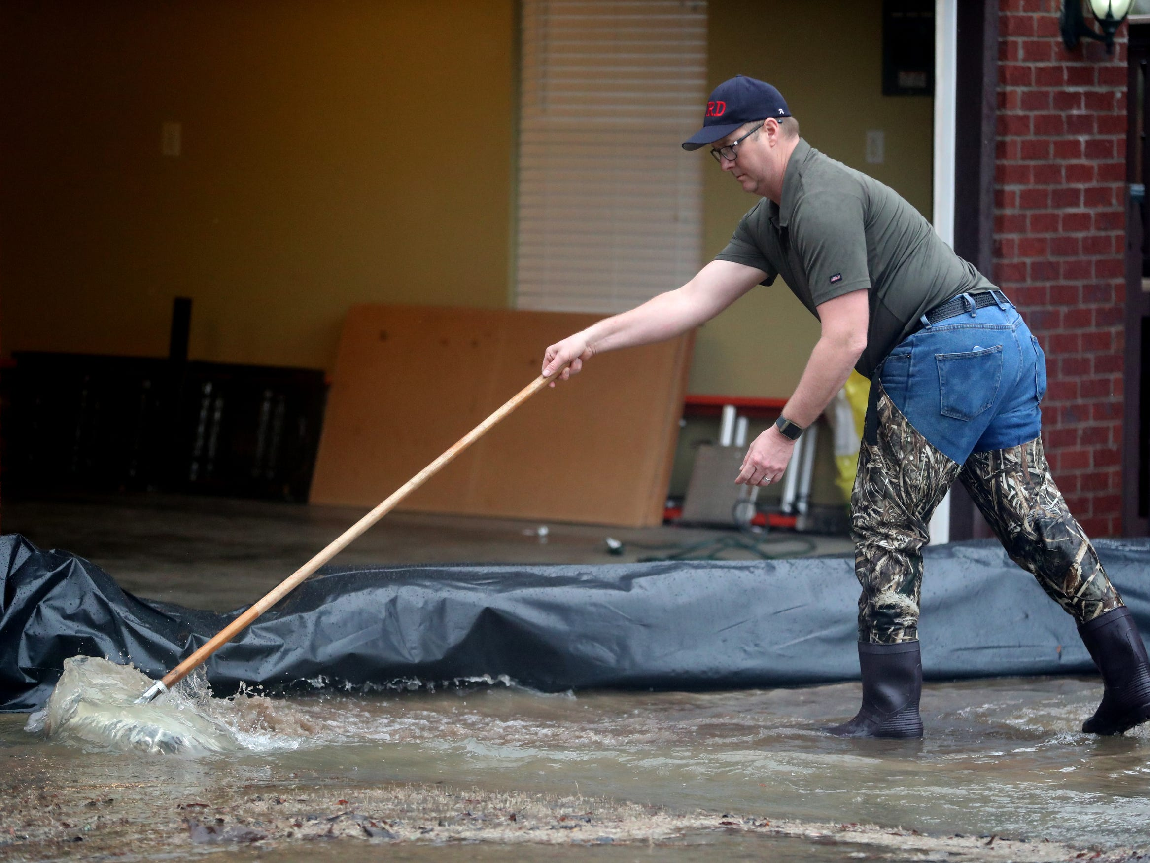 Charles Powell pushes water off of his driveway during flooding in Murfreesboro on Saturday, Feb. 23, 2019.