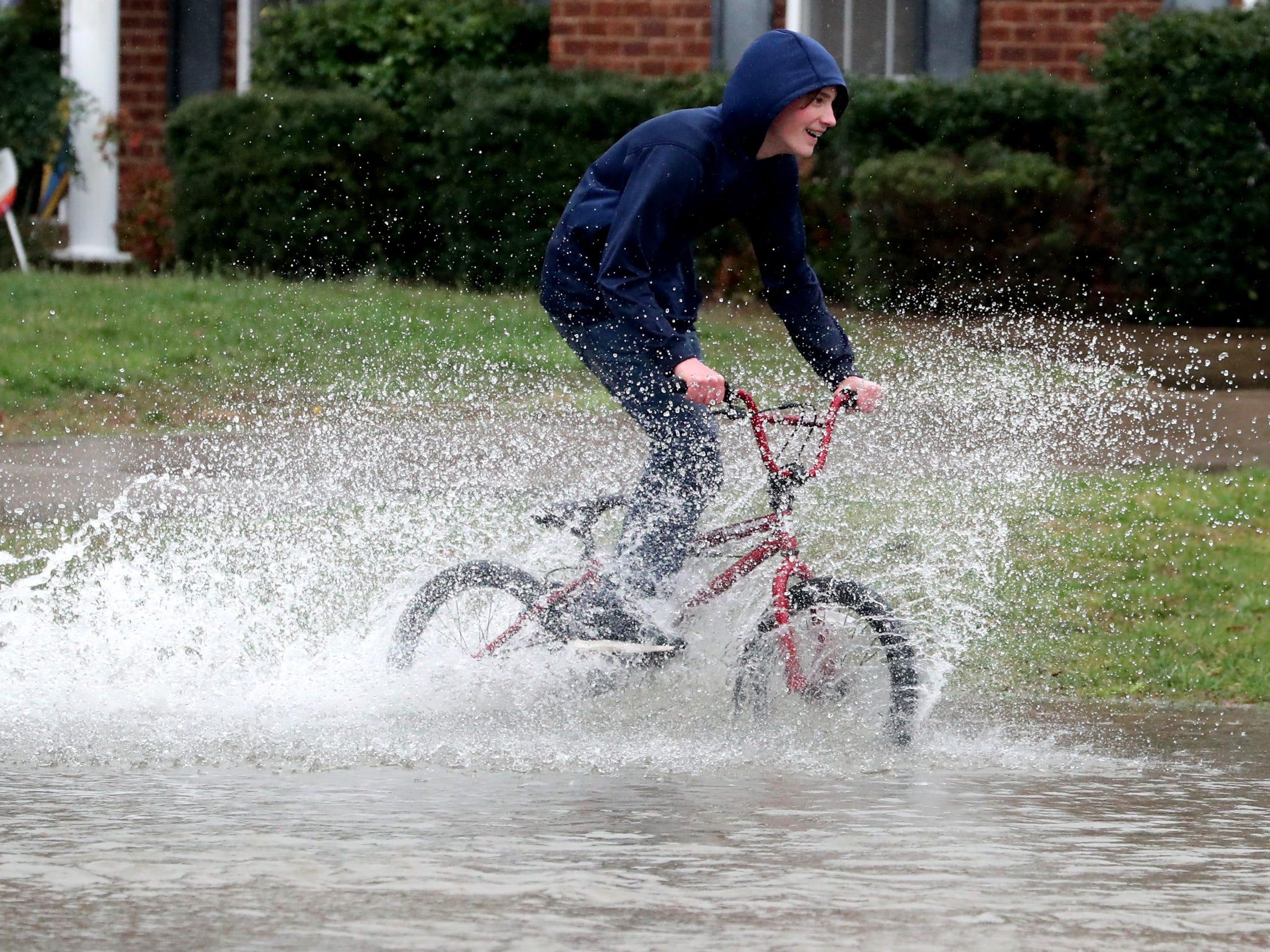 Joshua Schweikert, 14, drives his bike through rising flood waters in Murfreesboro on Saturday, Feb. 23, 2019.