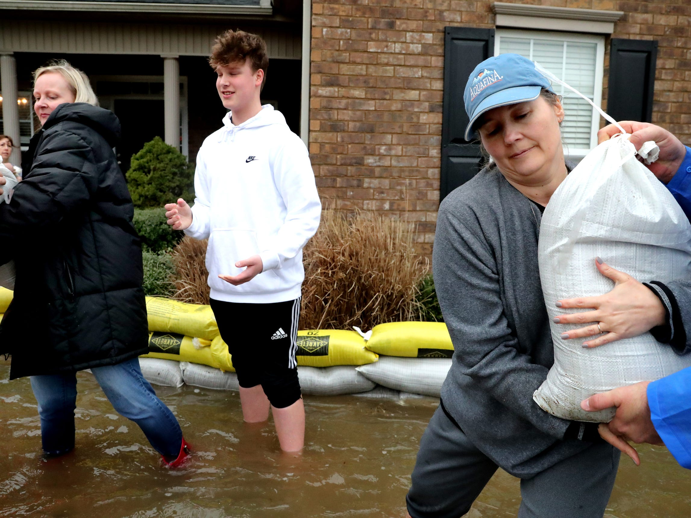 Teresa Garrison helps neighbors with sand bags during flooding in Murfreesboro on Saturday, Feb. 23, 2019.