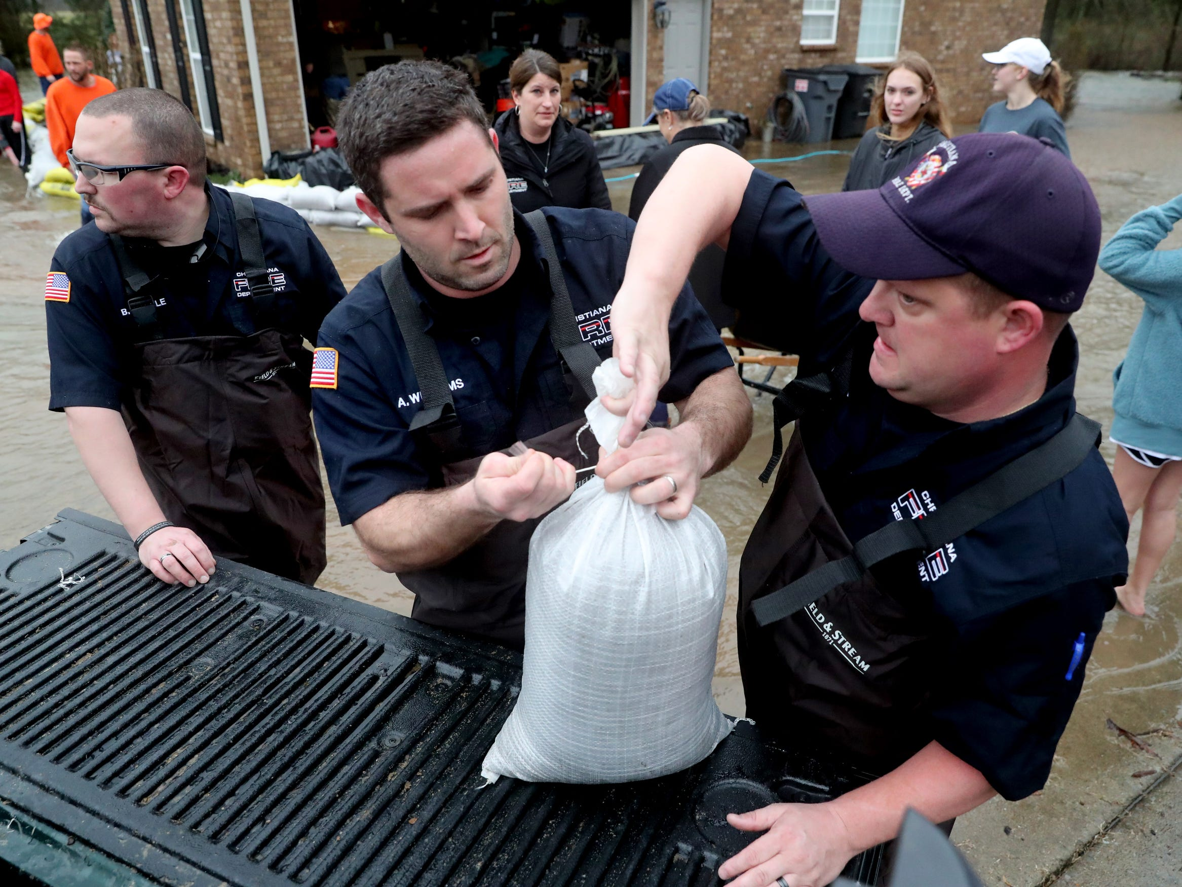 Christiana Fire Department members Mike Tappe (right), Allen Williams (middle), William Steele (left) prepare sand bags in Murfreesboro on Saturday, Feb. 23, 2019.
