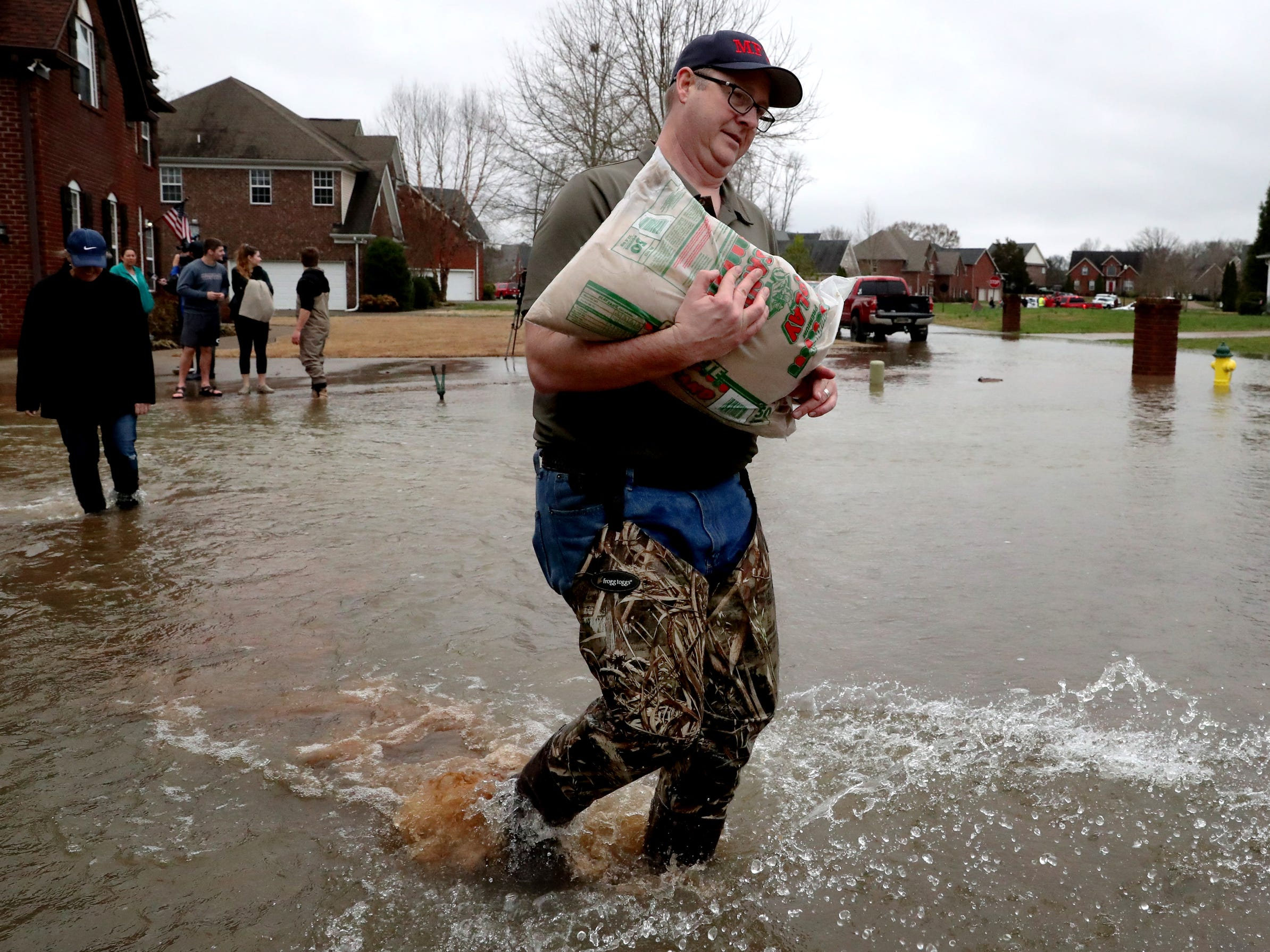 Charles Powell, a member of the City of Murfreesboro Fire Department, assists neighbors with sand bags during flooding in Murfreesboro on Saturday, Feb. 23, 2019.