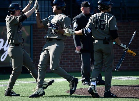 Vanderbilt outfielder Pat DeMarco (18) and Austin Martin (16) congratulate third baseman Jayson Gonzalez (99) as he scores during their game against Pepperdine on Feb. 24. Vanderbilt will play Florida in an SEC series, beginning Thursday.