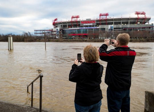 Kathy Pecylak and Steve Pecylak take pictures of the Cumberland River in Nashville on Sunday, Feb. 24, 2019. The Pecylak's said they were visiting from Palm Harbor, Fl. and wanted to see the height of the river one last time before flying home later today.