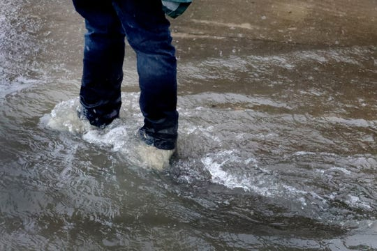 Water flows over the boots of Andrew Kellum along Steelson Way in Murfreesboro Saturday, Feb. 23, 2019, after days of rain have hit Middle Tennessee.