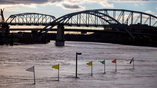 Flags sit partially submerged in the Cumberland River in Nashville on Sunday, Feb. 24, 2019.