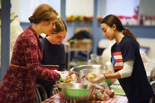 "Jana Siperstein-Szucs (L), the daughter of Barbra Siperstein, peels apples for the soup kitchen, together with Isabel Huber (age 12, c) of Montclair and Natalia James (age 12, R) of Montclair during the event of ""Healthy Backpack Program""  to serve needy children at Toni's Kitchen in Montclair on 02/24/19, in honor of the death of LGBTQ+ matriarch Barbra ""Babs"" Siperstein. With the support of the NJ LGBT Chamber of Commerce and in partnership with Toni's Kitchen, The Pride Network has launched a service effort to address food insecurity in Montclair."