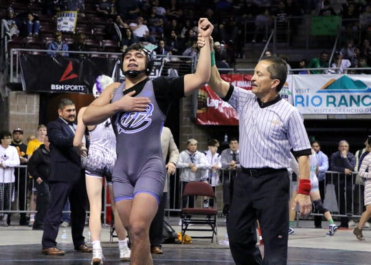 Carlsbad's Fabian Padilla has his hand raised after winning the state title in the Class 5A 170-pound division on Saturday.