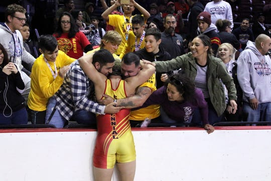 Centennial's Marco Rodriguez celebrates winning the Class 5A 182-pound division with his friends and family. This was the first state wrestling title for Centennial in school history.