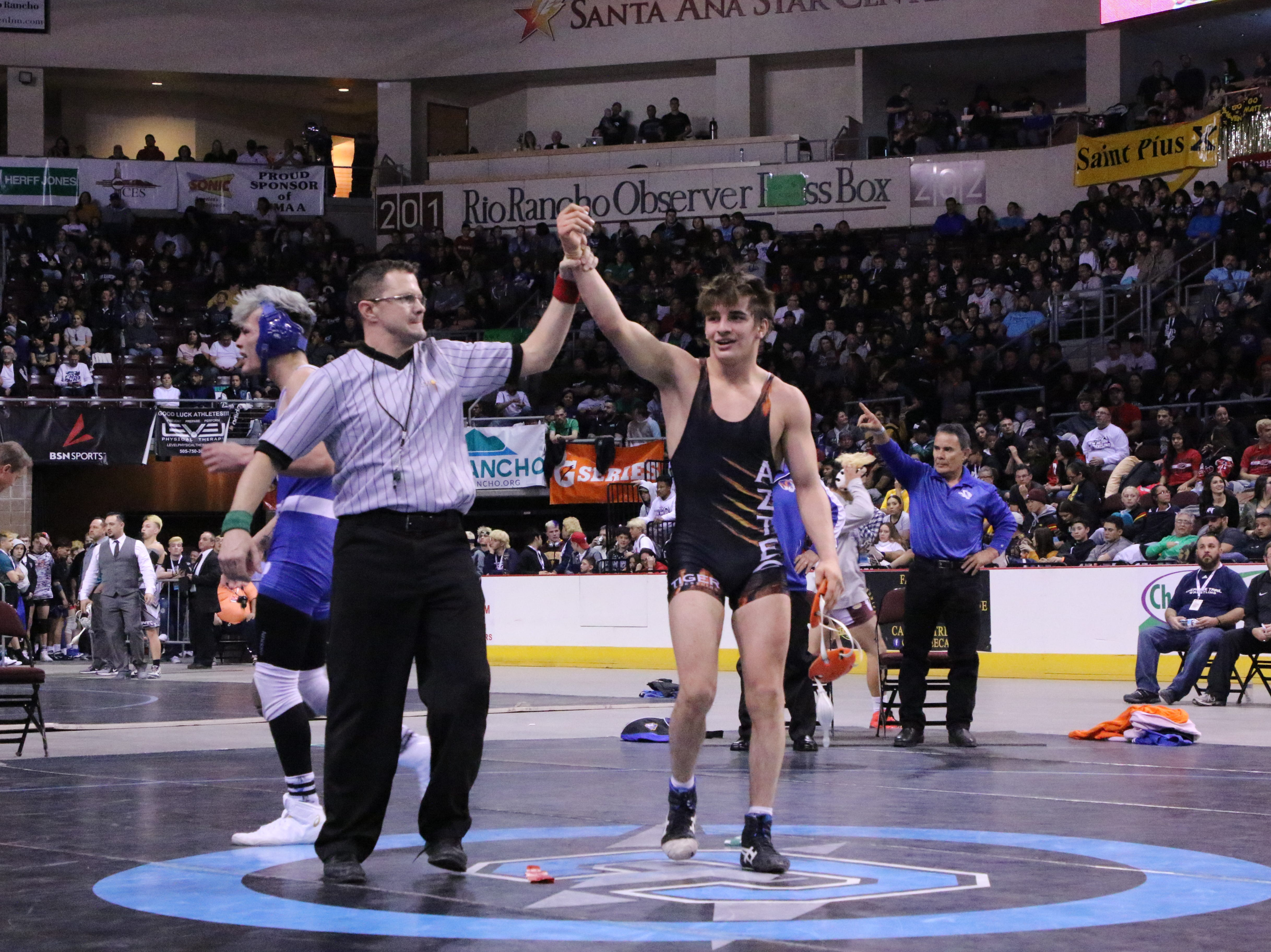 Aztec's Cody Candelaria has his hand raised after winning his championship match in the 2019 NMAA State Wrestling Championships.