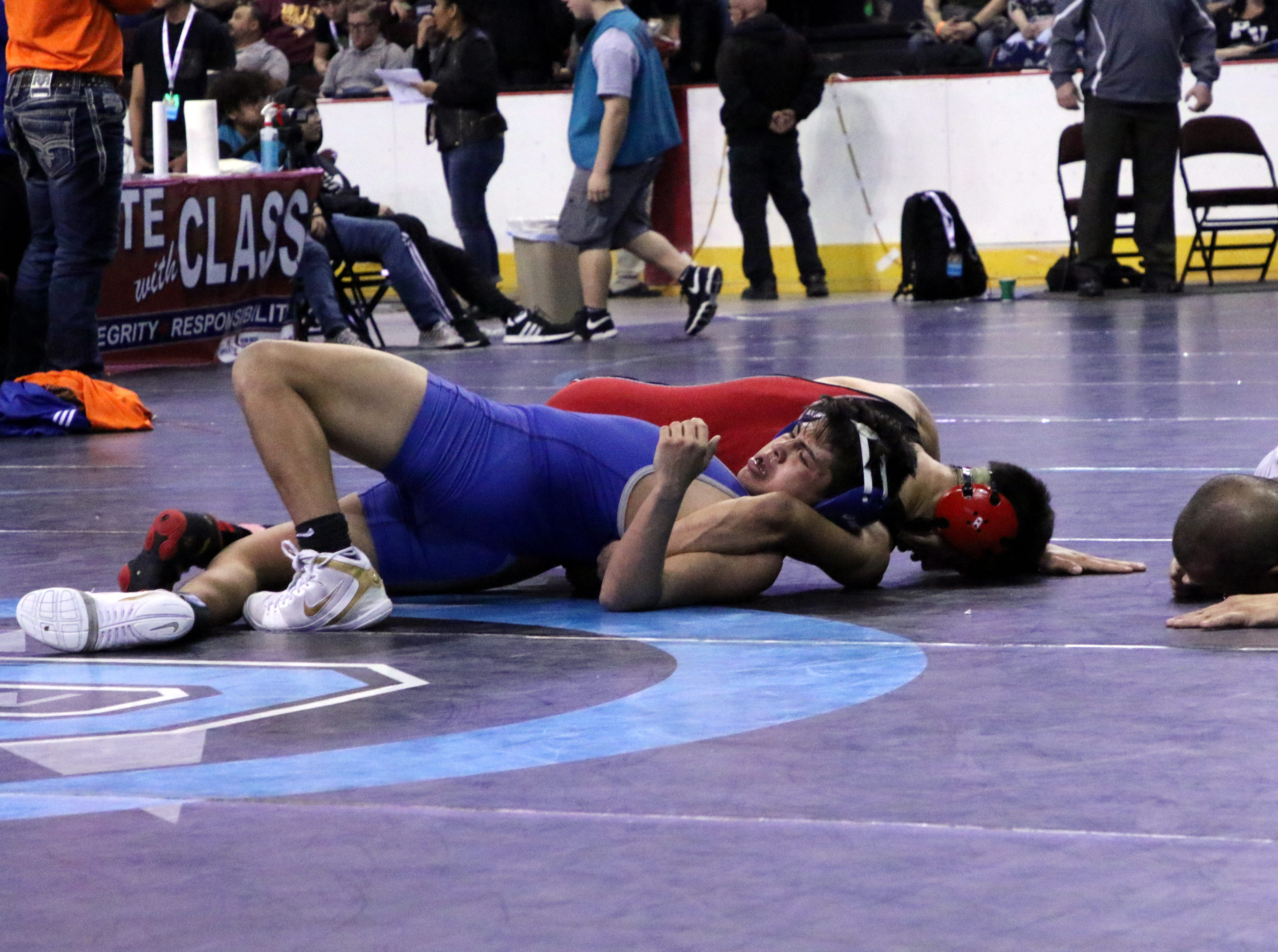 Matthew Najera tries to avoid a pinfall during his sixth-place match of the 2019 NMAA State Wrestling Championships.